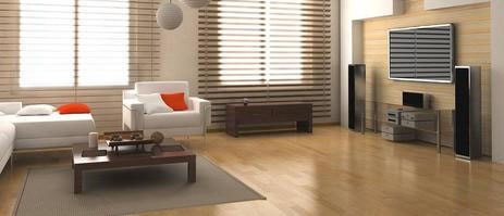 modern living room with white sofa and chair, coffee table, tv on wall and light coloured hardwood flooring