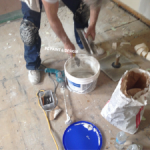 painter preparing drywall compound mix to repair ceiling before painting