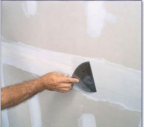 a painter repairing drywall before painting