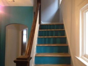 blue painted entrance and stairway with white walls and dark wood bannister