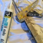 shows acrylic-latex caulk and caulking gun used by painters to seal gaps before painting