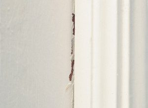 white wall with peeling and cracked paint to be repaired by painters