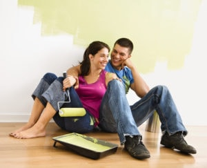 couple sitting on floor with half painted wall and paint roller and painting pan deciding on interior house painting