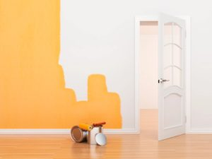 shows a white wall being repainted in a yellow paint colour