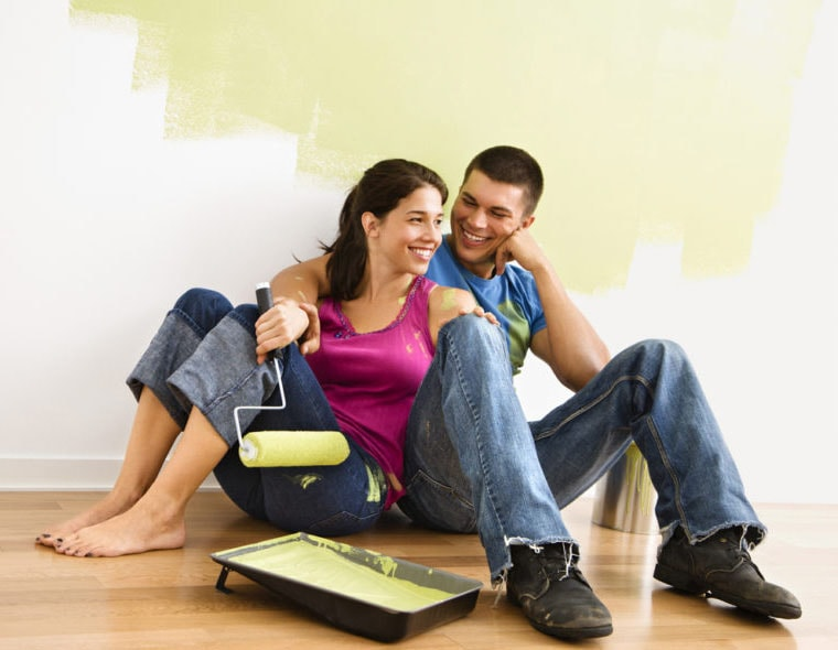 couple sitting down next to freshly painted wall of a house with paint pan and paint roller