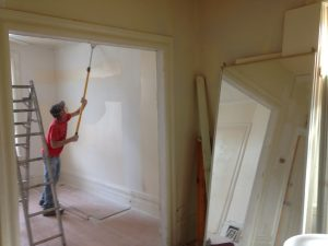 painter sanding walls after drywall and plaster repairs