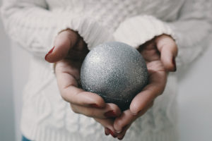 a woman holding metallic silver round ornament