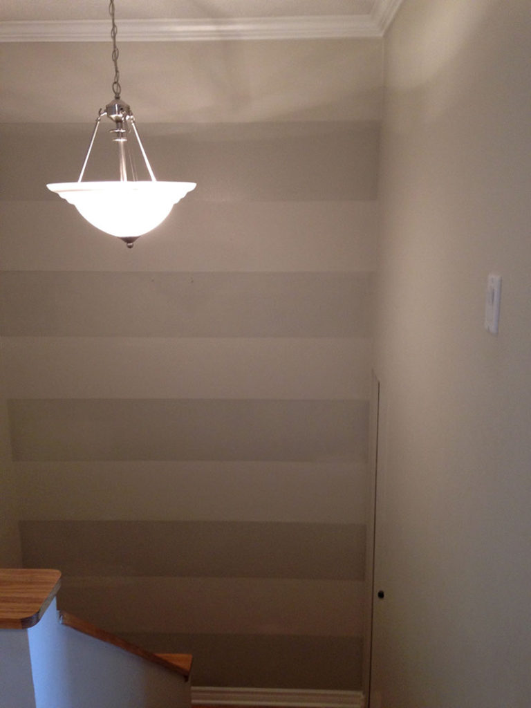 interior painting of wall with two gray paint colours to create stripes by professional painter PG PAINT & DESIGN Ottawa house painters