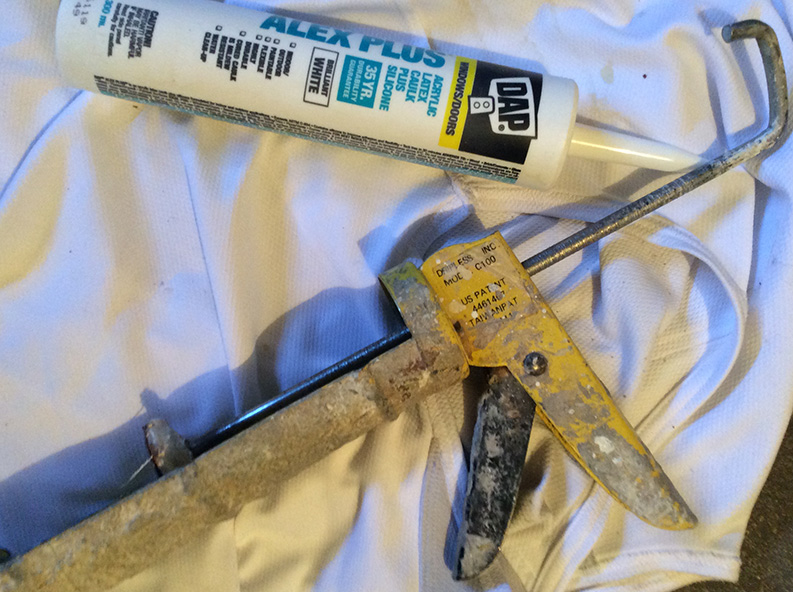 caulking and caulking gun for application around window seals and frames and baseboards and trim