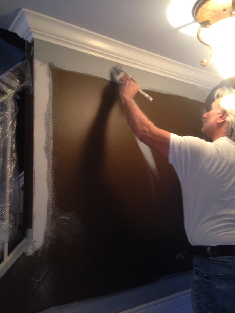 professional painter of PG PAINT & DESIGN applying first coat of paint primer to walls before painting with gray color